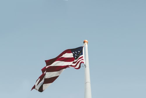 American flag waves in the wind against a light blue sky