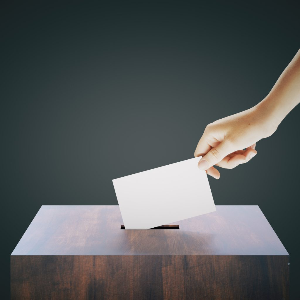 Hand with blank ballet casting vote into wooden ballot box on dark grey background. Voting concept. Mock up, 3D Rendering