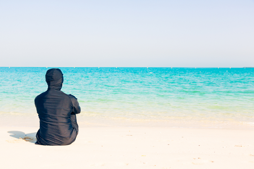 young woman wearing burkini sitting by the beach in dubai